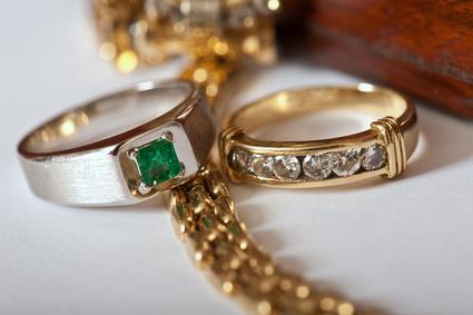 Eine Goldkette und zwei mit Edelsteinen besetzte Ringe