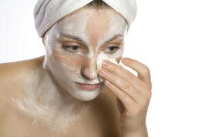 Eine Frau schmiert sich Creme ins Gesicht