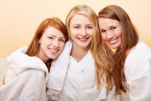 Drei lachende Frauen im Bad im Bademantel