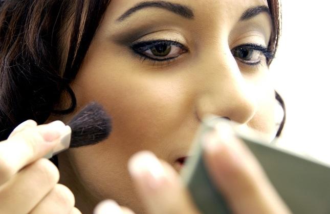 Eine junge Frau trägt Make-Up auf